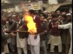 Crowd of people burn videos considered indecent
