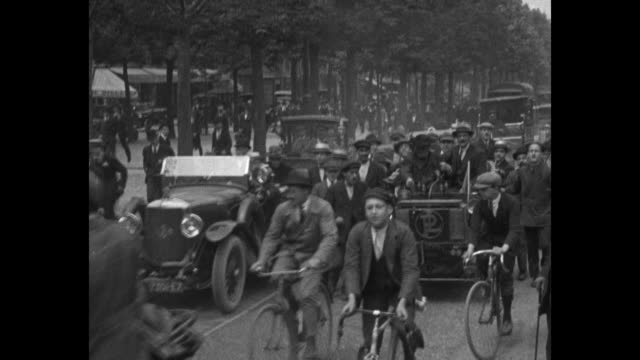 Crowd of people in cars and bicycles crowd alongside Abbe Paul Gavois motoring his 'Antoinette' antique car / the Abbe lights boiler at front of car...