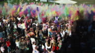 crowd of people throwing colored powder in the air