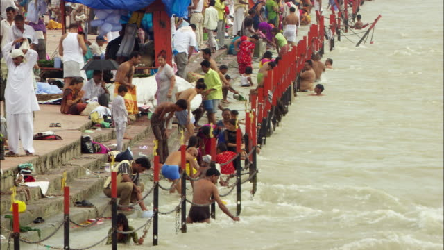 A crowd of people wade in the Ganges River. Available in HD.