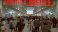 MS, T/L, crowd of people walking under Shanghai Railway station's information board, Shanghai, China