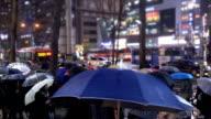 Crowd of people walking with umbrellas in rain on Gangnam Street, South Korea