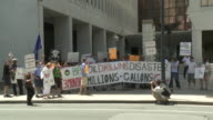 A crowd of picketers holds banners and signs in protest of BP Oil.