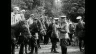 Crowd of Russian soldiers are disarmed by German soldiers / line of Russian cavalry sitting on horses are disarmed by German soldiers / German...
