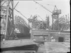 A crowd of shipyard workers arriving for work at the Bethlehem Fairchild Shipyard / moving shot of the shipyard with partially constructed ships /...