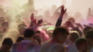 crowd of young people covered in colored powder and celebrating