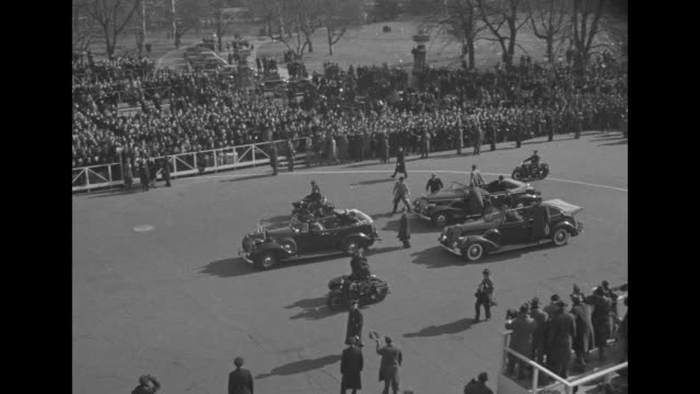 Crowd on east side of the US Capitol Building / threecar motorcade with Secret Service agents and motorcycles / soldiers wearing helmets in car with...