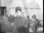 Crowd on pier waiting for Queen Mary / imitation Adolf Hitler down gangplank / phony Hitler salutes / soldiers down gangplank / Queen Mary tied up at...