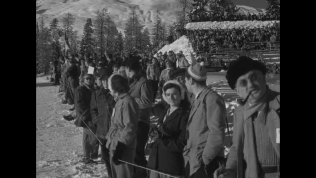Crowd sitting in bleachers on snowcovered slope / people lined up along bottom of ski jump watching / ski jumper skiing after landing / close view of...