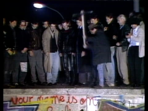 Crowd standing on Berlin Wall man swinging pick axe onto concrete Berlin Wall 09 Nov 89