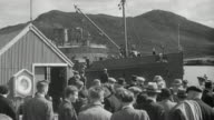 1943 MONTAGE Crowd waiting as ferry boat arrives at dock, passengers offloading and greeting families, and doctor asking guide for directions / Scotland, United Kingdom