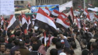 Crowd waving Egyptian flags and milling about in Tahrir Square / Cairo Egypt