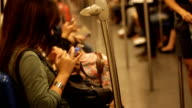 Crowded people in the mass public transportation using their phone while waiting