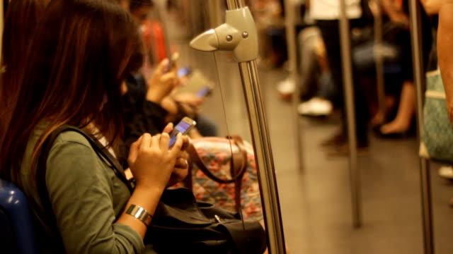 Voll Menschen in der Masse öffentlichen Verkehrsmittel, während Sie mit Ihrem Telefon
