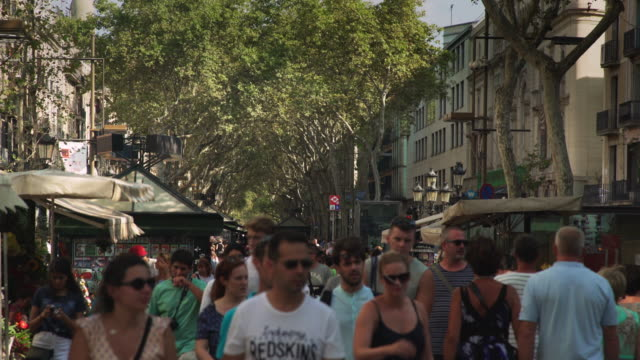 Crowded Ramblas of Barcelona at sunny day. People walking across this world famous promenade