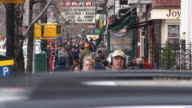 A crowded sidewalk on Sixth Avenue in Manhattan.  It is early spring and people are bundled up and walking up the street.