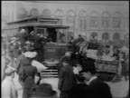 B/W 1906 crowded trolley on busy San Francisco street with people walking wagons
