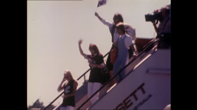 crowds at the Airport waiting for Abba to arrive chanting 'We Want ABBA and holding up ABBA posters ABBA exit plane and wave from top of steps...