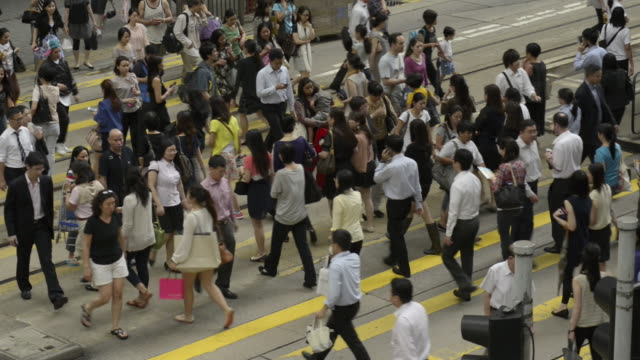 Crowds crossing Des Voeux Road.Central shopping district.