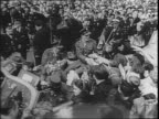 Crowds gather at City Hall / American soldier Charles 'Commando' Kelly rides in car through crowd shakes hands lifts baby / Sergeant Kelly holds up...