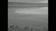 Crowds in stands at Yankee Stadium / Yogi Berra at bat against Cleveland Indians / CU man leaning forward in seat in stands / Berra hits home run /...