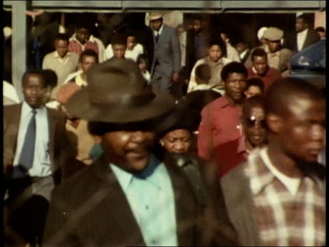Crowds of black men and women fill the shabby streets on their way to work or on their way home / newsboy man selling newspapers on sidewalk with...