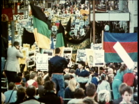 Crowds of enthusiastic demonstrators carrying a wide variety of banners flags placard signs and portrait posters of Nelson Mandela AntiApartheid...