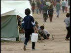 Crowds of ethnic Albanian refugees walk through refugee camp during time of conflict Kosovo 03 May 99
