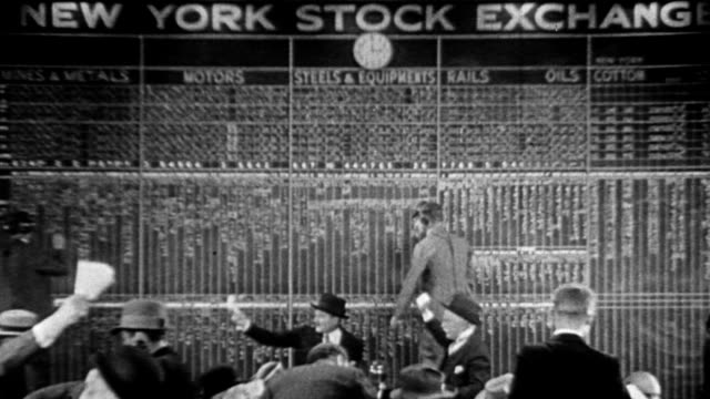 crowds of people standing outside bank / stock traders at the New York Stock Exchange board traders waving papers in air and writing on board / CU...