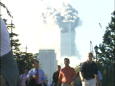 Crowds of people walking along the West Side Highway away from the burning World Trade Center building Smoke pouring from the North Tower 1 Various...