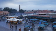 Crowds of shoppers walk through Djemaa el-Fna on a rainy night.