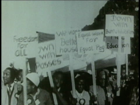 Crowds of South African men and a few women demonstrating in civil rights protest against Apartheid carrying signs written in English AntiApartheid...