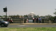 Crowds of tourists and traffic in Washington DC with Jerrferson Memorial in background.