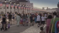 Crowds of tourists walk down a Jersey Boardwalk in Ocean City NJ on a summer day.  The American flag lining the boardwalk and people spend time with their families.
