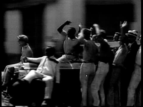 Crowds running down avenue of Havana street during revolution / people riding on car past camera / rioters smashing furniture in front of building /...