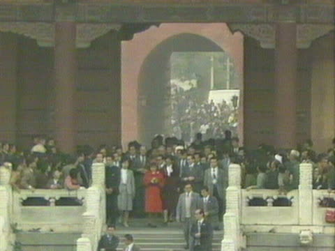Crowds rush to see Queen Elizabeth as she enters the Forbidden City during her visit to Beijing October 1986