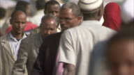 Crowds walk along a busy street in Addis Ababa. Available in HD.