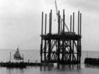 Crowds watch as a partly constructed cooling tower for the Dungeness power station is towed from the harbour at Folkestone