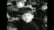 Crown Prince Hiro's first day of primary school in Tokyo / large crowd of young children in an assembly hall / CU Prince Hiro sitting with other...