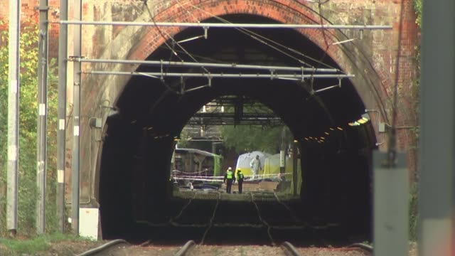 First victim named ENGLAND London Croydon EXT Forenisc police officers and forensic tent seen through train tunnel with cordon tape across tracks...