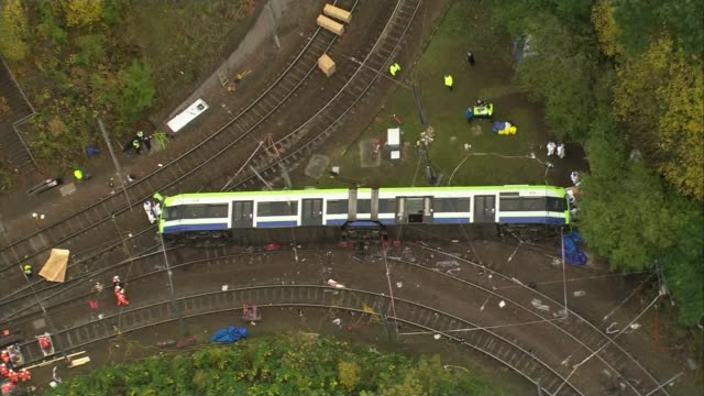 First victim named EXT tram lying on side with interview overlaid SOT AIR VIEW Tram wreckage and rescue workers in overalls at scene AIR VIEW...