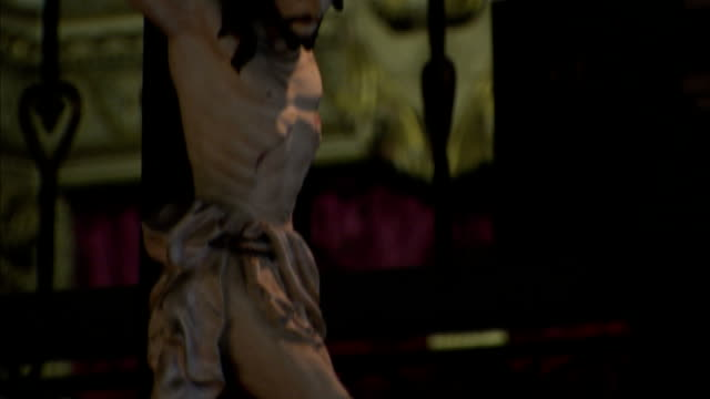 Crucifixes hang near the altar of a cathedral. Available in HD.