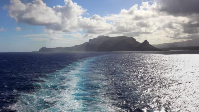 A cruise ship leaves a wake as it departs the Hawaiian island of Kauai