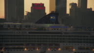Cruise ship pulls into port in front of the new yorker building and the manhattan skyline