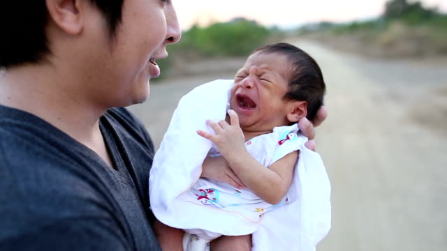 Crying newborn and father.