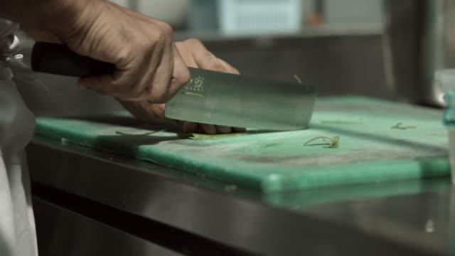 CU_Chef cutting spring onion in kitchen