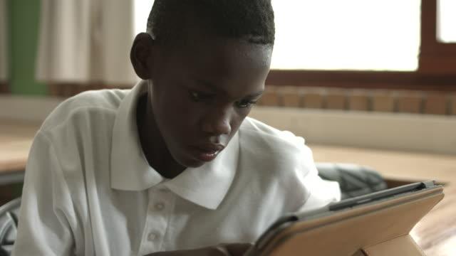 CU_Schoolboy working on digital tablet in classroom