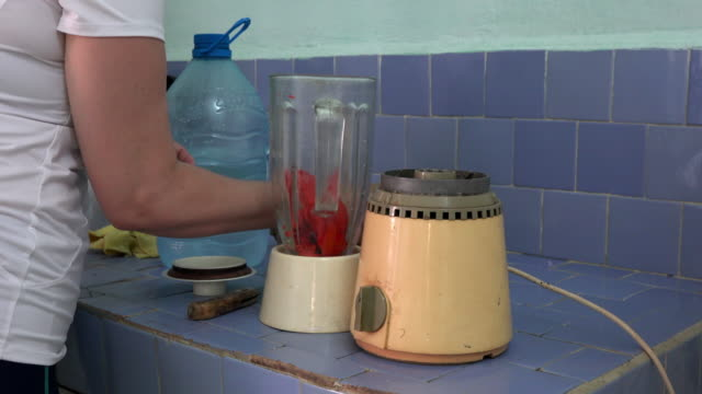 Cuba: Woman prepares a mamey or sapote milk shake in an old traditional Russian mixer