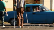 LS of Cuban Man with Crutches & Pedestrians crossing street in Havana