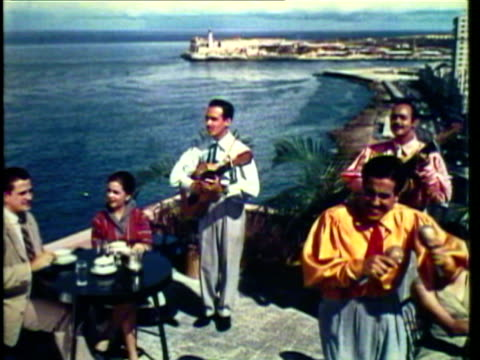 1953 WS MS Cuban mariachis entertain guests with song at outdoor cafe / Cuba / AUDIO